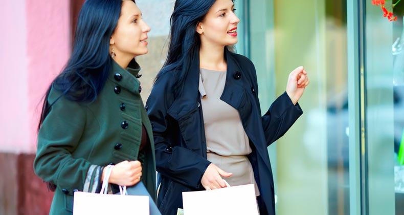 Two women shopping looking in shop window © Olesia Bilkei/Shutterstock.com
