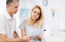 Man and woman looking at their bill with disappointment | iStock.com/skynesher