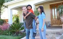 Family standing outside front door | Stephen Coburn/Shutterstock.com