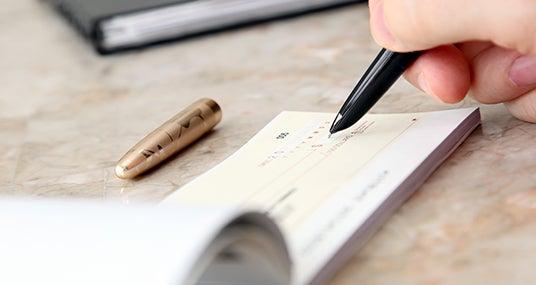 Writing in checkbook © NAN728/Shutterstock.com