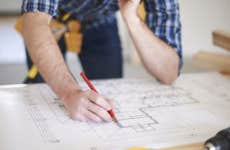 Man making changes to home blueprint © iStock.com