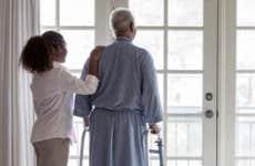 Nurse resting hand on senior's shoulders | Terry Vine/Blend Images/Getty Images