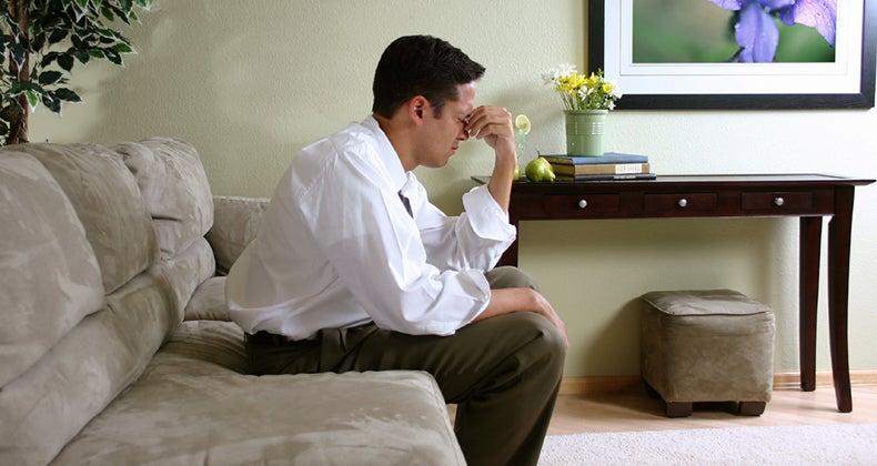 Man pinching the bridge of his nose © iStock