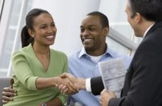 Couple shaking hands with financial adviser | Blend Images – Ariel Skelley/Brand X Pictures/Getty Images