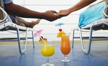 Couple holding hands on cruise deck chairs | LWA/Dann Tardif/Blend Images/Getty Images