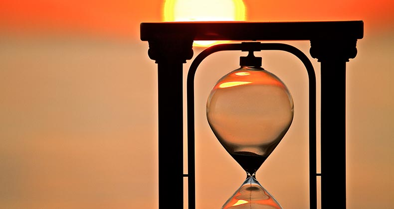 Hourglass and sunset background | iStock.com/Leslie Achtymichuk