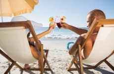 Couple on beach with drinks © wavebreakmedia/Shutterstock.com