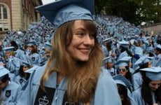 Graduating woman in blue cap and gown | TIMOTHY A CLARK/AFP/Getty Images