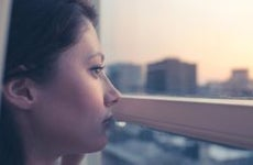 Woman looking out of her apartment window | by Dornveek Markkstyrn/Moment/Getty Images