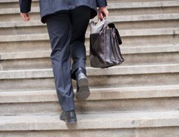 Man with briefcase climbing up the stairs