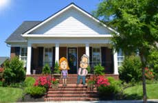 New England style house with cartoon characters standing on the steps © jessicakirsh/Shutterstock.com; © Lorelyn Medina/Shutterstock.com