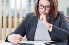 Businesswoman using calculator in office
