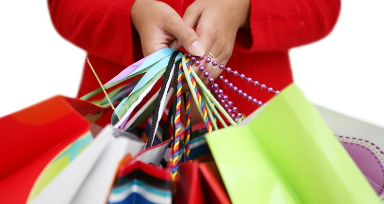 Woman holding many shopping bags © Stephen Coburn/Shutterstock.com