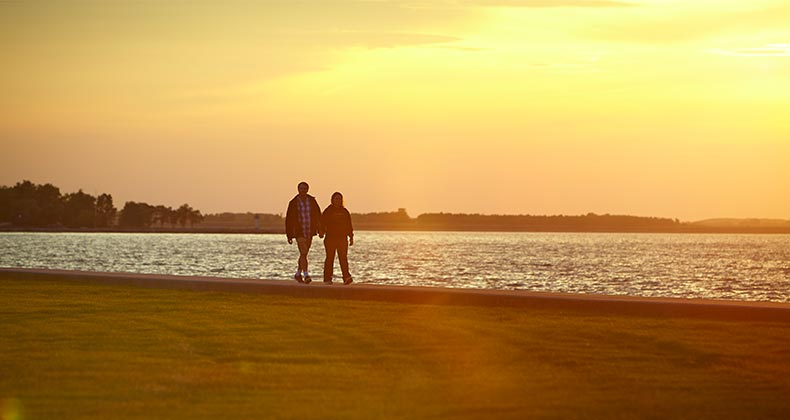 Couple walking along beach in Toledo, Ohio | Destination Toledo CVB
