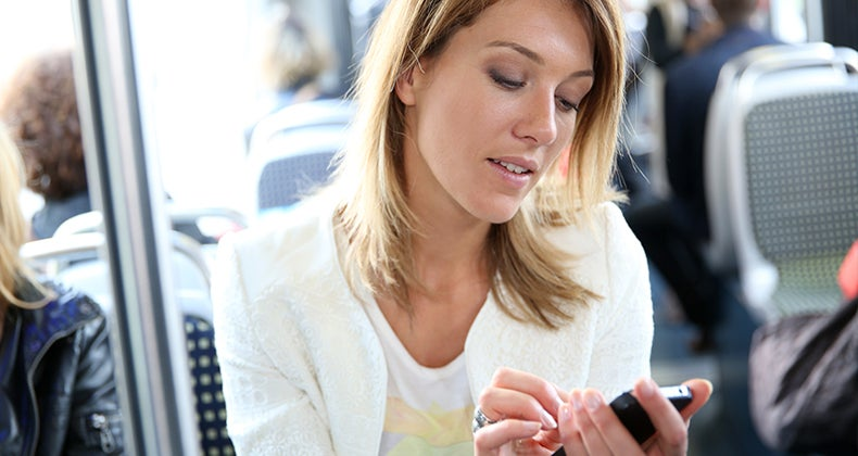 Smiling young woman in city train using smartphone © Goodluz/Shutterstock.com