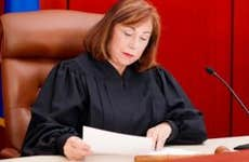 Senior female judge reading paperwork   iStock.com/Alina Solovyova-Vincent