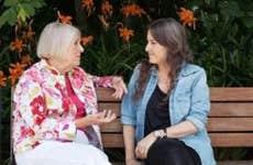 Two women sitting on a bench, talking   Allison Michael Orenstein/Getty Images