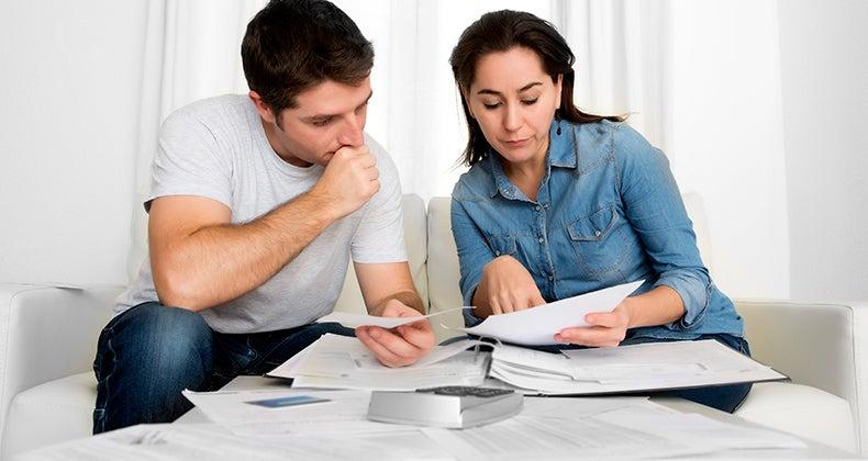 Young couple worried sorting bills, paperwork © iStock