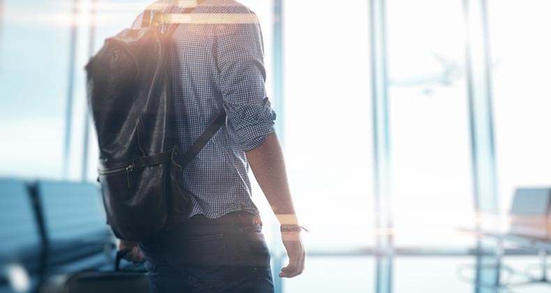 Man at the airport holding his luggage © iStock