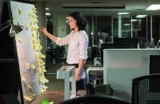 Woman working late, sorting sticky notes on board   Hero Images/Getty Images