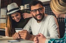 3 millennials talking, holding credit card | Georgijevic/Getty Images