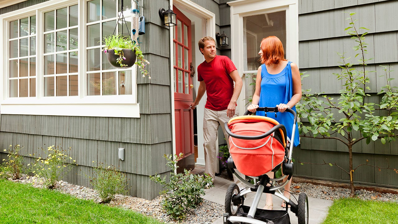 Father and mother leaving house with baby in stroller
