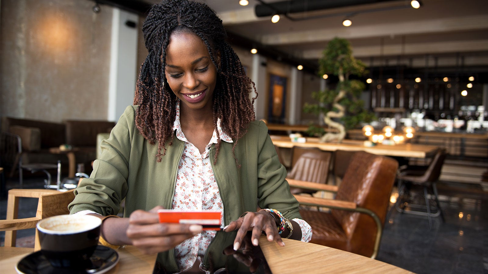 Woman at coffee shop putting credit card in her purse