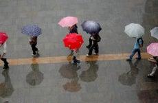 people walking through the rain with umberellas