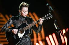 Miley Cyrus on stage playing the guitar