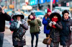 People bundled up walking down the street