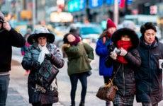 People bundled up walking down the street