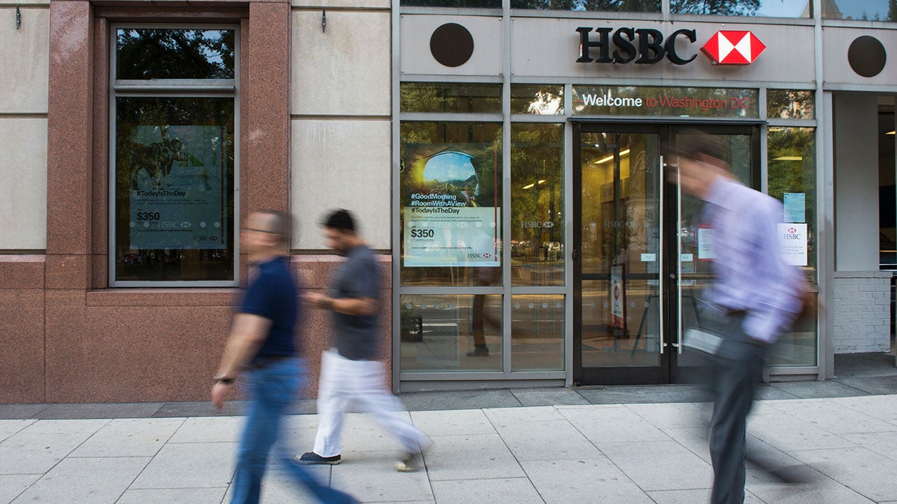 People walking past an HSBC Bank