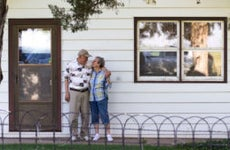 Older couple stand in front of house