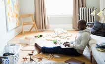 Man using laptop sitting on living room floor