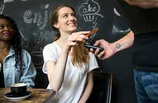 Woman paying cafe check with smartphone
