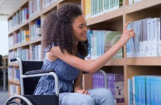 Student with wheelchair looking through college library