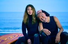 An older surfer couple hug at the beach