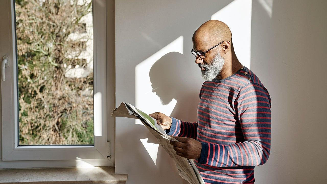 Bearded man reading newspaper