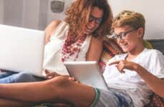 Mother and pre-teen son sit together on bed working on laptop and tablet