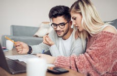 Young couple analyzing paperwork and computer