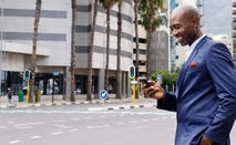 African American businessman smiling at cell phone while walking in the city