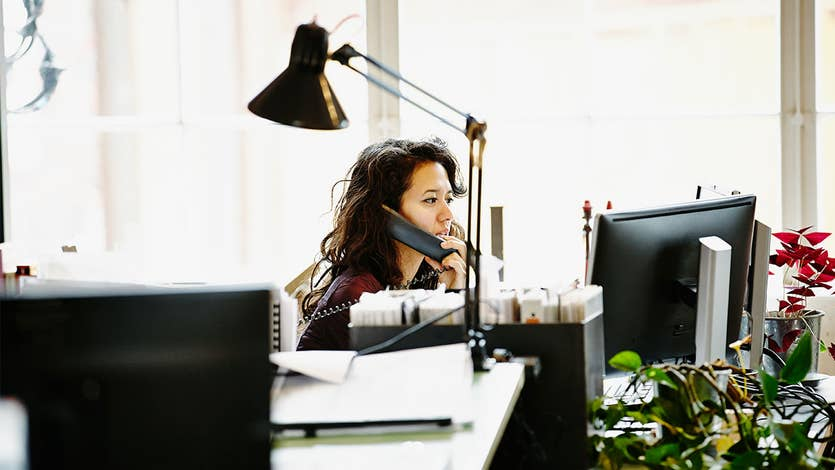 Woman talks on the phone in office
