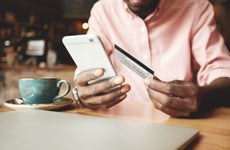African American man using credit card on smartphone