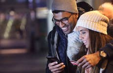 Couple checks cellphone in the cold