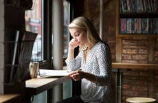 Woman in coffeeshop reviewing paperwork