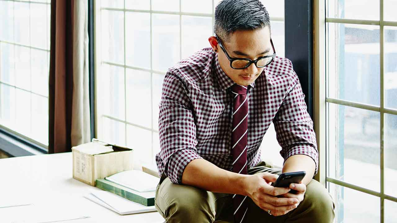 Professional young man working on smartphone in office
