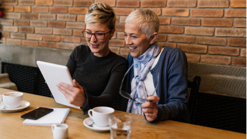 Woman and her older mother look together at tablet in cafe