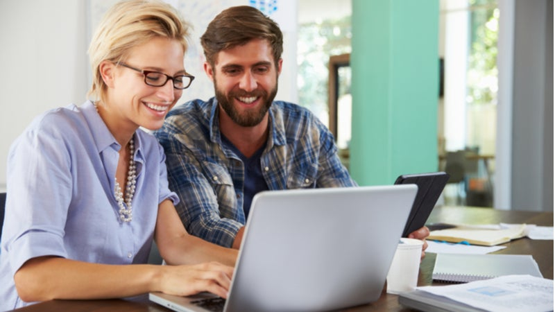 Couple happily works on laptop together