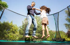 Father and daughter bouncing on trampoline