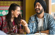 Young Indian couple laughing over meal